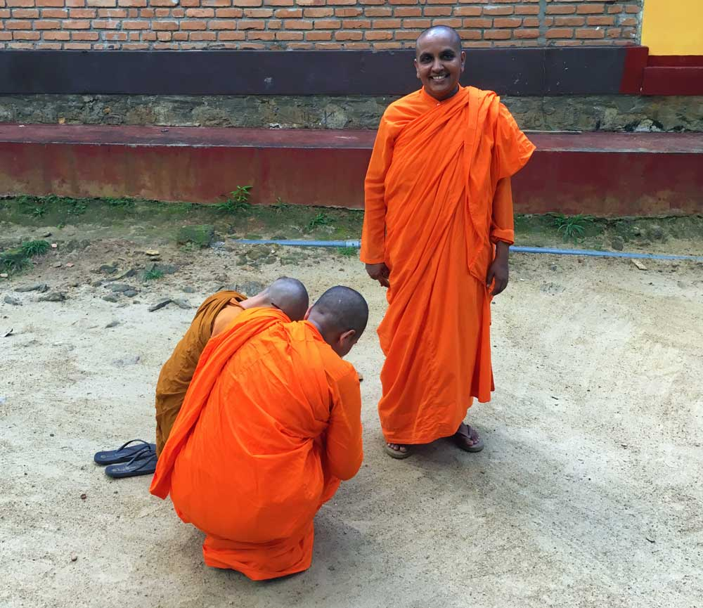 Two Buddhist nuns bow respectfully to their teacher, she smiles at the camera